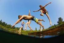 Enfants espiègles sautant outre du dock dans le lac ensoleillé d'été — Photo de stock