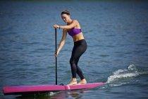 Joven mujer paddleboarding en océano soleado - foto de stock