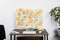 Клейкие заметки, охватывающие компьютер в офисе — стоковое фото