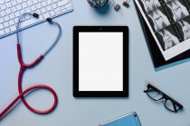 View form above digital tablet surrounded by stethoscope and x-rays — Stock Photo
