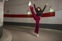 Портрет уверенной молодой женщины, танцующей в туннеле — стоковое фото