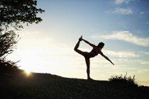 Силуэт женщины, практикующей королевскую позу йоги — стоковое фото