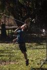 Беззаботный мальчик прыгает в разбрызгиватель на солнечном заднем дворе — стоковое фото