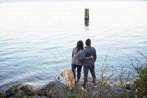 Ласковая пара с собачьими объятиями, наслаждающаяся видом на озеро — стоковое фото