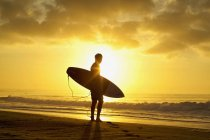 Silhouetted male surfer with surfboard on tranquil, sunset ocean beach — Stock Photo
