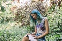 Jeune femme aux cheveux bleus écrivant dans un journal dans le parc — Photo de stock