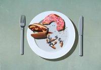 Perros calientes, rosquillas y colillas de cigarrillos a medio comer en el plato - foto de stock