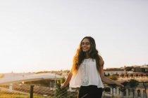 Porträt einer lächelnden jungen Frau im sonnigen Stadtpark — Stockfoto