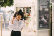 Felice giovane donna che cammina sul marciapiede urbano — Foto stock