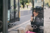 Happy young woman talking on smartphone at bus stop — Stock Photo