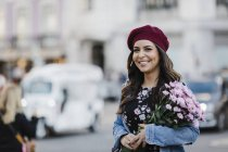 Portrait of happy young woman in beret with flower bouquet on urban street — Stock Photo