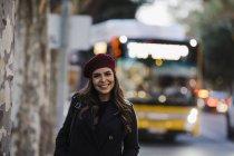 Ritratto di giovane donna sicura di sé in berretto sul marciapiede urbano — Foto stock