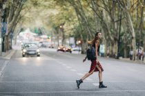 Young woman crossing city street — Stock Photo