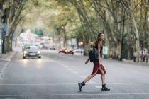 Mulher nova que cruza rua de cidade — Fotografia de Stock
