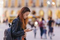 Молодая женщина с рюкзаком на городском тротуаре с помощью смартфона — стоковое фото