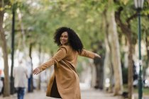 Portrait of carefree young woman dancing on sidewalk — Stock Photo