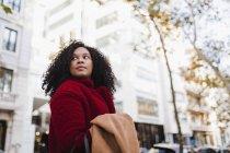 Giovane donna guardando oltre la spalla sulla strada urbana — Foto stock