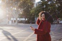 Портрет впевненості, усмішка молодої жінки зі смартфоном на сонячній міській вулиці — стокове фото