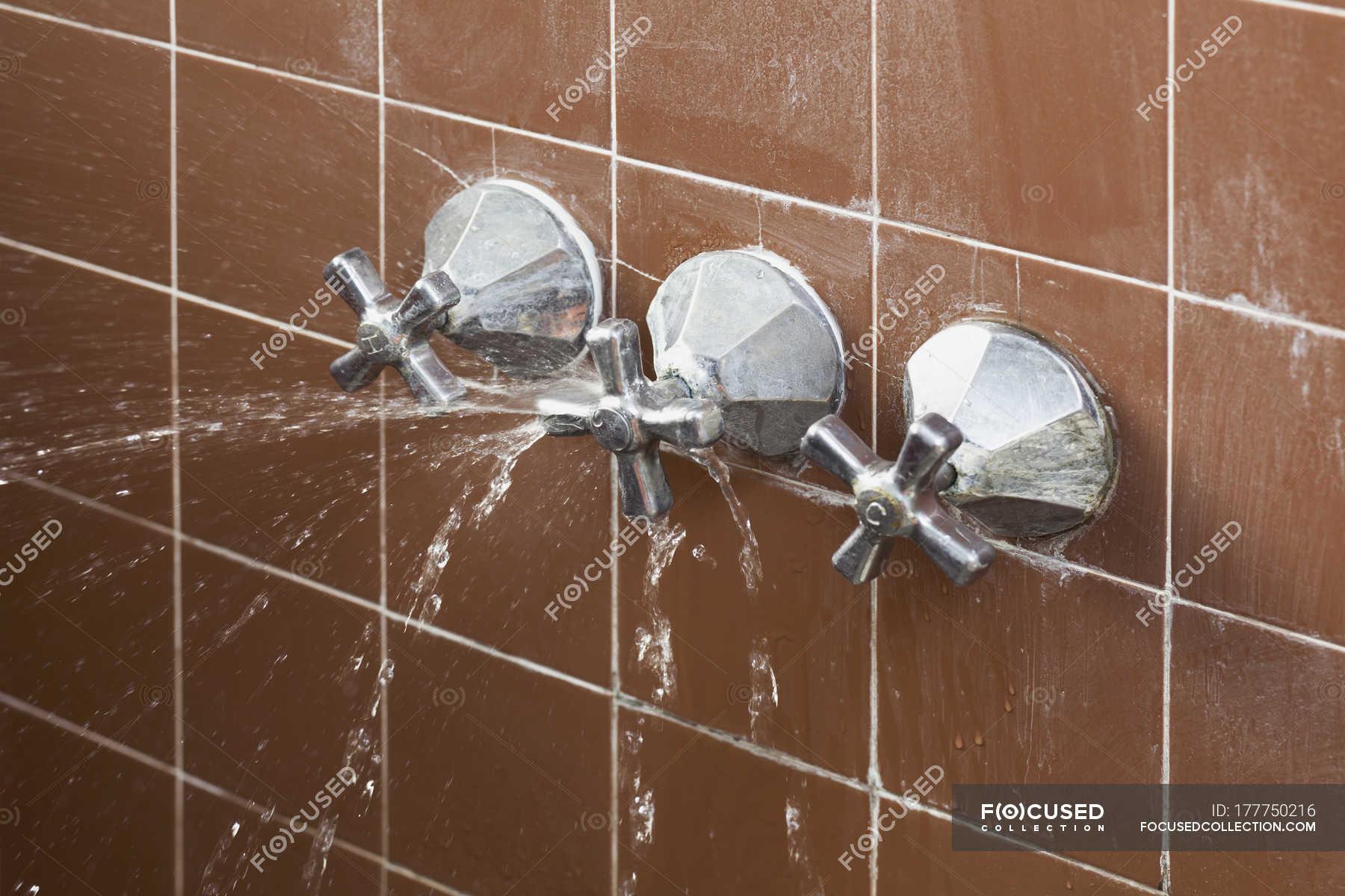Broken shower faucet handle spraying leaking water — Stock Photo ...