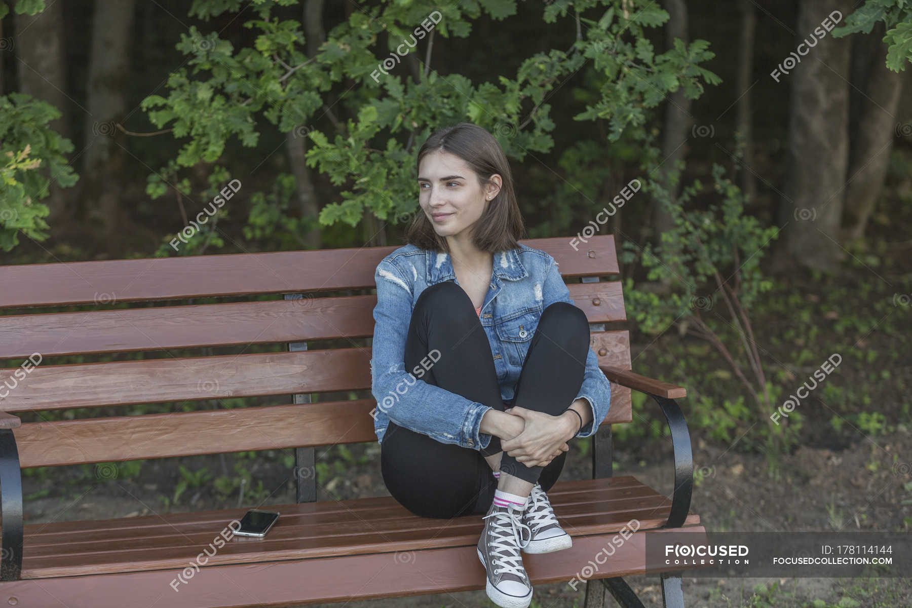 Incredible Smiling Young Woman Sitting On Wooden Bench Against Trees In Ocoug Best Dining Table And Chair Ideas Images Ocougorg