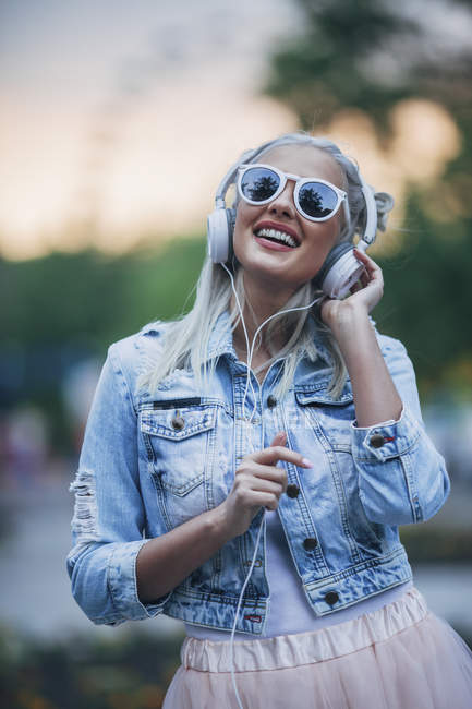 Happy fashionable woman wearing sunglasses listening to music with headphones — Stock Photo