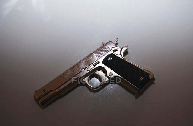Top view of gun on white table — Stock Photo
