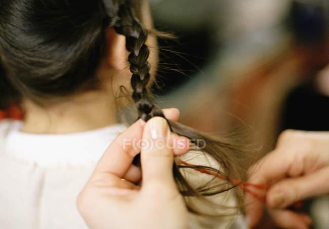 Cortar as mãos femininas trançando o cabelo da menina — Fotografia de Stock