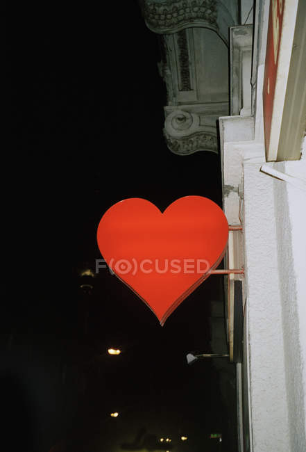 Exterior view of building corner with heart sign plate over night sky - foto de stock