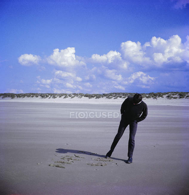 Mann schreibt mit dem Fuß am Ufer in Sand — Stockfoto