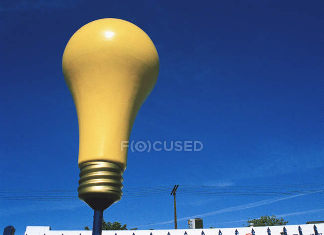 Yellow light bulb sculpture over blue sky — Stock Photo
