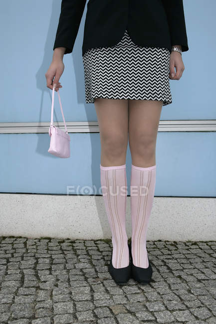 Low section of woman holding purse and standing against a wall — Stock Photo