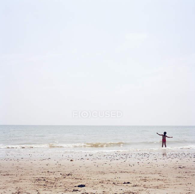 Rückansicht des Kindes stehend mit ausgebreiteten Armen in Wellen zum Surfen am sonnigen Sandstrand — Stockfoto