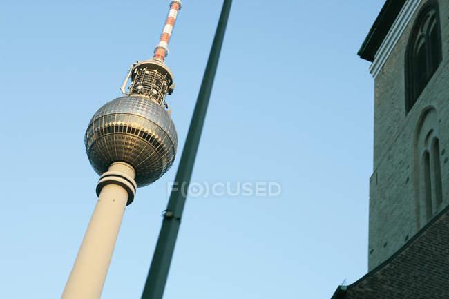 Vista dal basso della torre illuminata dal sole televisione su sfondo di cielo blu — Foto stock