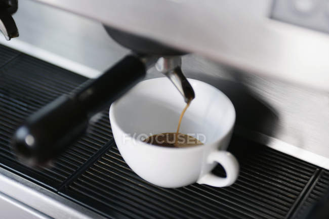 Close up view of espresso pouring from coffee machine in cup — Stock Photo