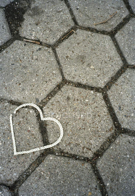 High angle view of plastic heart on concrete pavement — Stock Photo