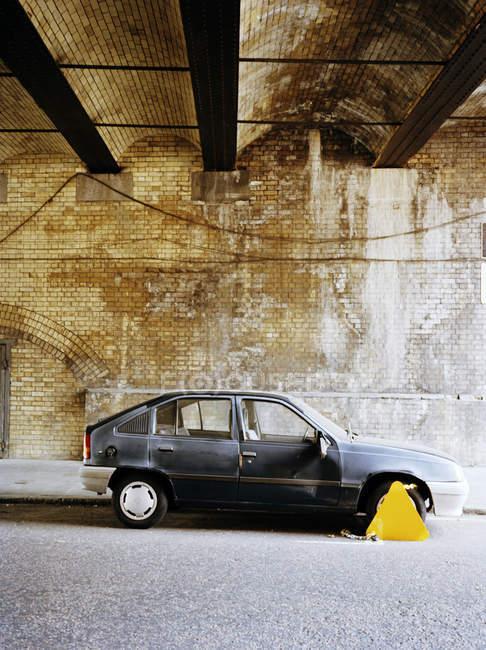 Заброшенный автомобиль с blocker колесо под мостом — стоковое фото