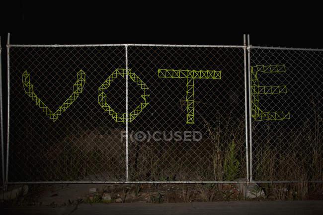 Inscrição de VOTE em cerca de arame à noite — Fotografia de Stock