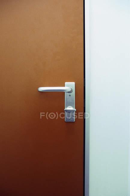 Закрыть вид металлической дверной ручки на коричневой двери — стоковое фото