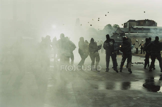 Obscured view of group of rioters throwing stones at police — Stock Photo