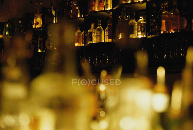 Obscure view of rows of bar glasses and bottles at shelves — Stock Photo