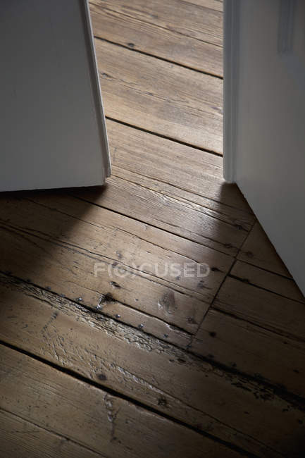 Crop of open double doors and wooden floor — Stock Photo