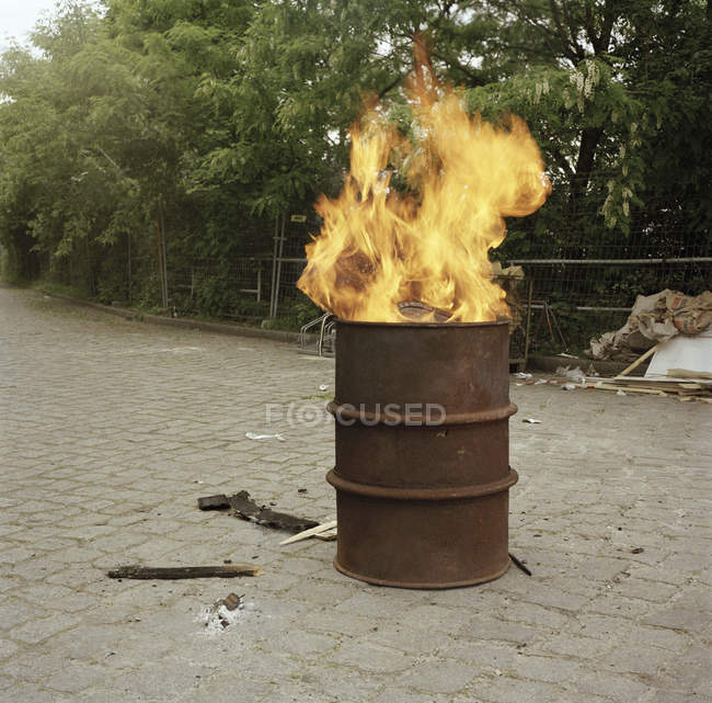 Fire burning in barrel at park alley — Stock Photo