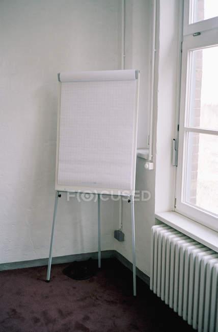 Белая доска с чистыми бумажными простынями в углу комнаты — стоковое фото
