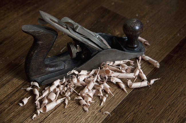 Close up view of wood planing tool and shavings on wooden table — Stock Photo