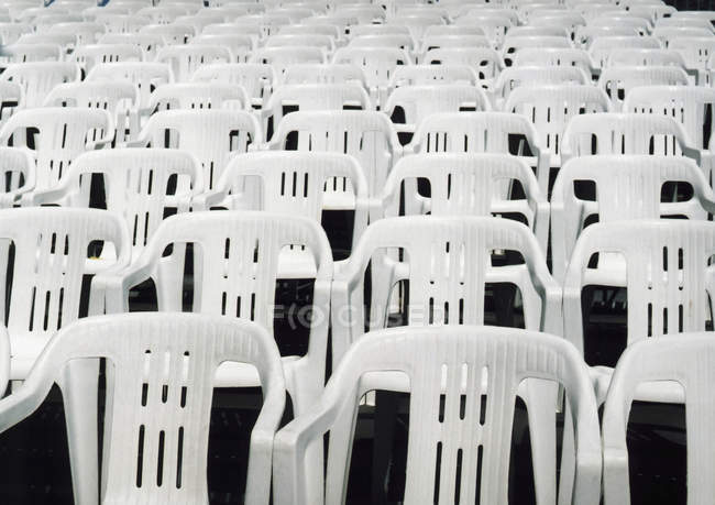 Rows of empty white plastic chairs — Stock Photo