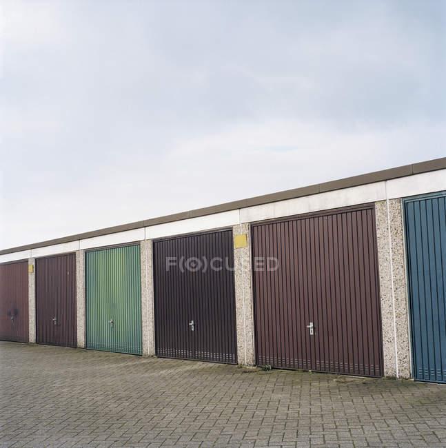 Fila de unidades de almacenamiento comunes sobre cielo gris - foto de stock