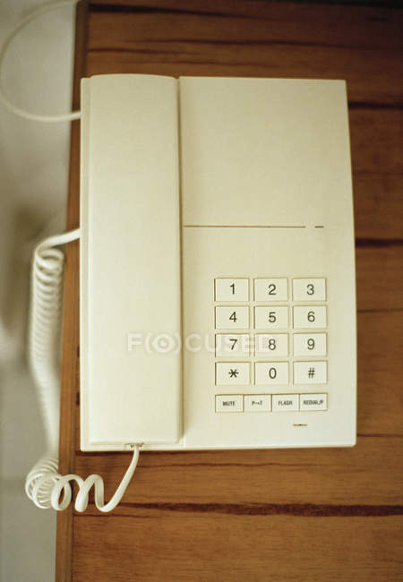 Вид зверху білий настільний телефон на дерев'яні таблиці — стокове фото