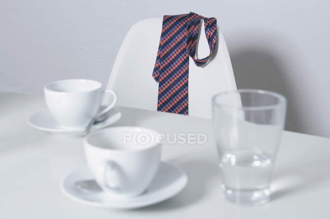 Necktie hanging on chair at table with coffee cups and empty glass — Stock Photo