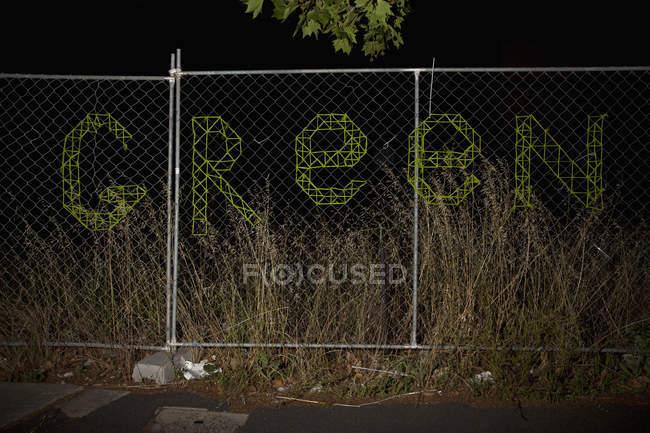 Inscrição VERDE em cerca de arame à noite — Fotografia de Stock