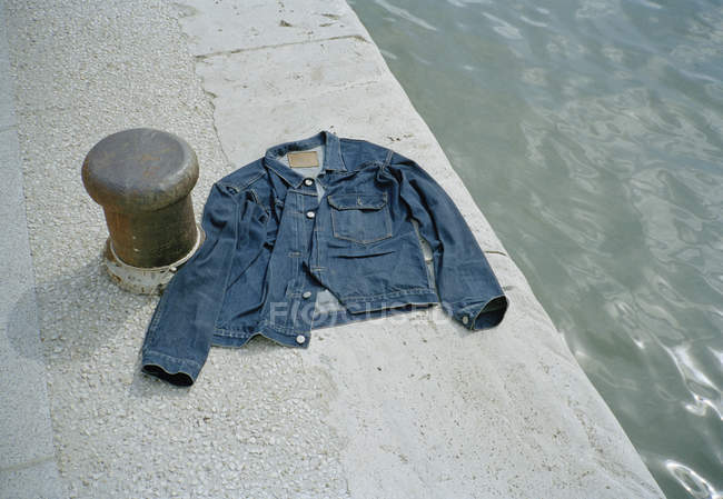 High angle view of denim jacket on riverbank — Stock Photo